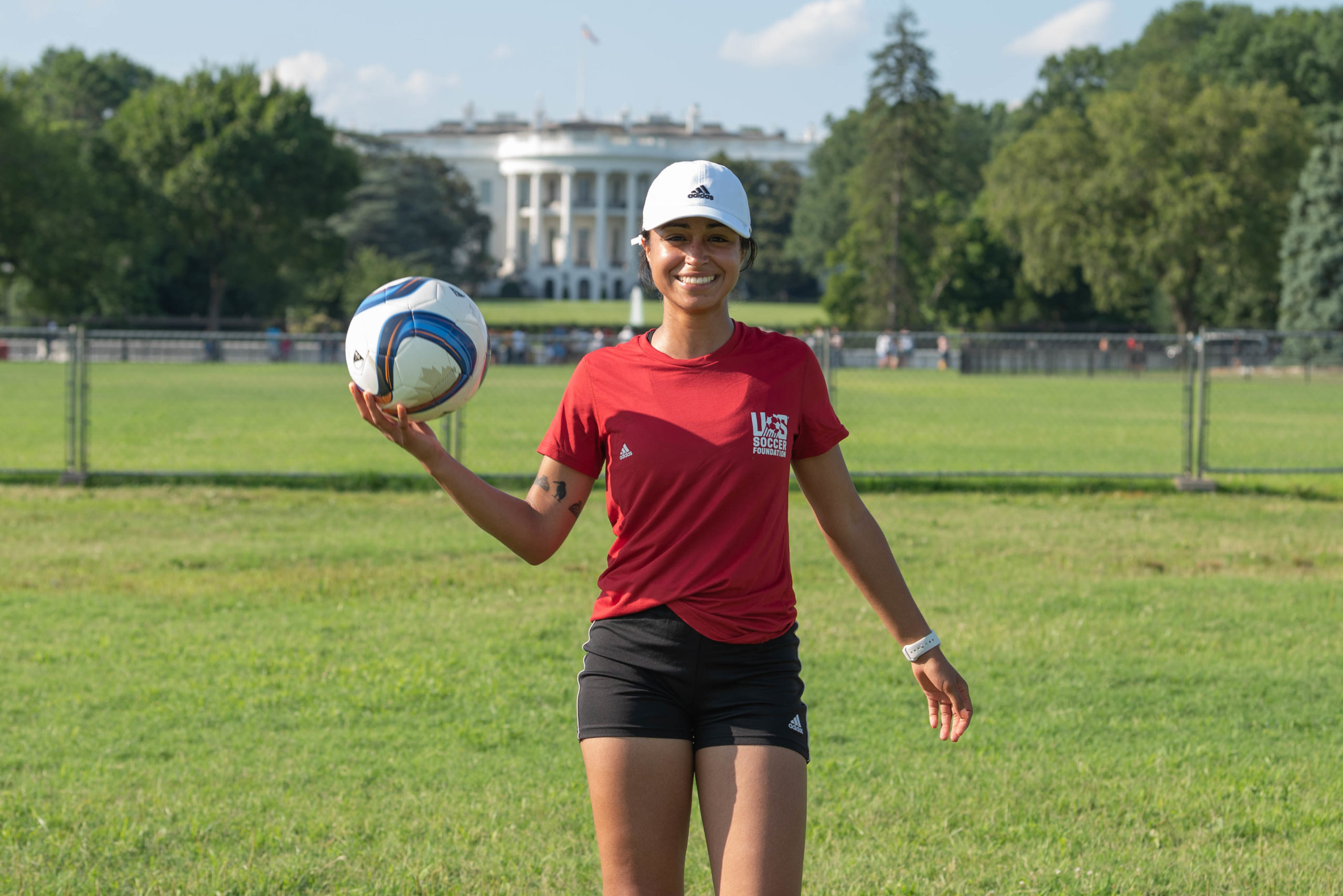 alana pictured in front of white house with soccer ball in red shirt and white hat